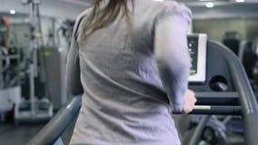 Frau, die auf Tretmühle in der Gymnastik läuft stock footage