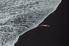 Frau, die auf tropischen Strandschwarzsand im weißen Bikini legt lizenzfreies stockbild