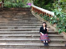 Frau, die auf tropischer Szene der Treppe sitzt Stockbild