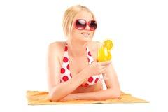 Frau, die auf Tuch liegt und ein Cocktail hält Stockfoto