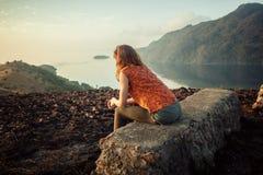 Frau, die auf ungewöhnlichem Felsen bei Sonnenaufgang sitzt Stockbild