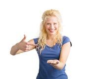 Frau, die auf unsichtbares objet zeigt, das sie hält Stockbild