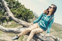 Frau, die auf Wacholderbuschbaum sitzt Stockfoto