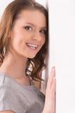 Frau, die auf Wand über weißem Hintergrund sich lehnt Stockfotos