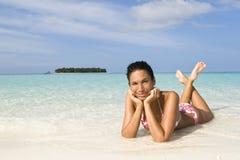 Frau, die auf weißem Sandstrand suntanning ist Lizenzfreies Stockbild