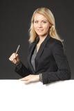 Frau, die auf whiteboard sich lehnt Stockfotografie