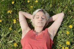 Frau, die auf Wiese schläft Stockbilder