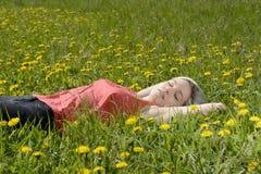Frau, die auf Wiese schläft Stockbild