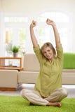 Frau, die auf Wohnzimmerfußboden ausdehnt Stockfotos