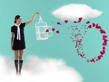 Frau, die auf Wolke mit captureing Fliegenherzen des Käfigs steht Valentinesday lizenzfreies stockfoto