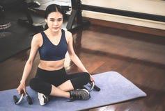 Frau, die auf Yogamatte in der Eignungsturnhalle sitzt lizenzfreie stockfotografie