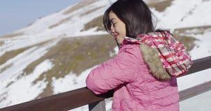 Frau, die auf Zaun auf Bergen sich lehnt stock footage