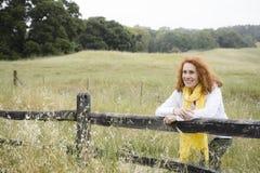 Frau, die auf Zaun sich lehnt lizenzfreies stockfoto