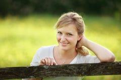 Frau, die auf Zaun sich lehnt Stockfotografie