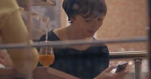Frau, die auf Zelle sich verständigt, wenn Freund im Café getroffen wird stock video footage