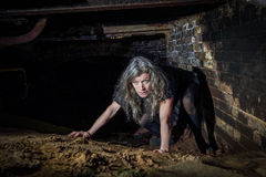 Frau, die in aufgegebenes Gebäude kriecht Lizenzfreies Stockbild