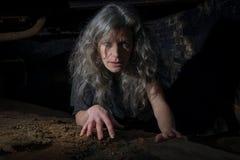Frau, die in aufgegebenes Gebäude kriecht Stockbilder