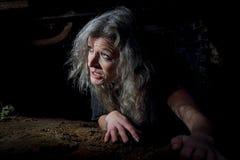 Frau, die in aufgegebenes Gebäude kriecht Lizenzfreie Stockfotos