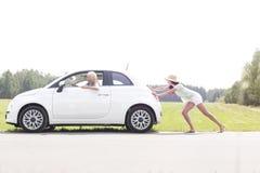Frau, die aufgegliedertes Auto auf Landstraße drückt Stockbild