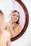 Frau, die aufmerksam im Spiegel betrachtet Stockfotos