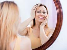 Frau, die aufmerksam im Spiegel betrachtet Lizenzfreies Stockfoto