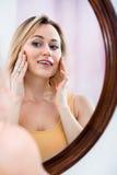 Frau, die aufmerksam im Spiegel betrachtet Lizenzfreie Stockfotos