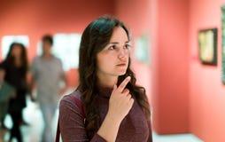 Frau, die aufmerksam Malereien im Kunstmuseum betrachtet stockfotografie