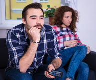 Frau, die aufpassendes Fernsehen mit Freund sich langweilt Stockfotografie