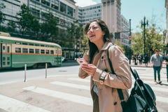 Frau, die aufwärts schaut und Handy hält stockfotografie