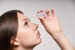 Frau, die Augenheilkunde Eyedropper anwendet Glaukomaugenverhinderung menschliche Visionsserumwäsche unter Verwendung Krankheitsk stockbild