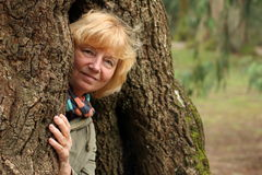Frau, die aus Baum herauskommt Stockfoto
