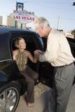 Frau, die aus der Limousinen-Mann-Unterstützung heraus tritt Stockfotos