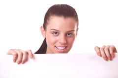 Frau, die aus unbelegtem Vorstand oder Papier heraus schaut Stockfotos