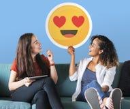 Frau, die ausdrucksvollen Emoticon auf einer Couch hält stockbild