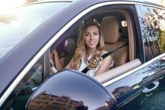 Frau, die Auto fährt und die Kamera betrachtet stockfoto