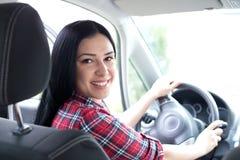 Frau, die Auto fährt und zurück schaut Lizenzfreies Stockfoto