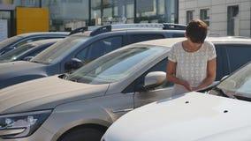 Frau, die Auto für das Kaufen in der wirklich wünschenden Verkaufsstelle wählt stock footage