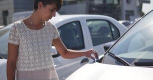 Frau, die Auto für das Kaufen in der wirklich wünschenden Verkaufsstelle wählt stock video footage