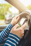 Frau, die Auto fährt und Mitteilung auf Smartphone simst Stockfotografie
