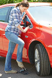 Frau, die Auto-Reifen mit Fuß-Pumpe aufbläst stockfoto