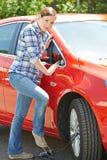 Frau, die Auto-Reifen mit Fuß-Pumpe aufbläst stockfotos