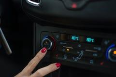 Frau, die Autoklimaanlage einschaltet stockfotos