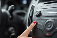 Frau, die Autoradio einschaltet lizenzfreie stockfotografie