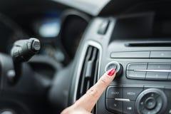 Frau, die Autoradio einschaltet stockbild