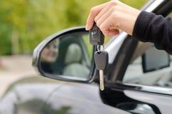 Frau, die Autoschlüssel außerhalb des Fahrzeugs hält Stockfotografie