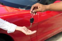 Frau, die Autotaste vom Verkäufer empfängt Lizenzfreies Stockbild