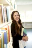 Frau, die am Bücherregallächeln sich lehnt Stockfotos