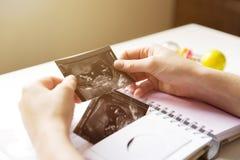 Frau, die Baby ` s Sonogram in Baby ` s erstes Jahr-Gedächtnisbuch setzt Stockbilder