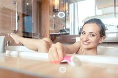 Frau, die Bad in der Hotelbadewanne ergreift ihren Rasierapparat für Haar hat lizenzfreies stockbild