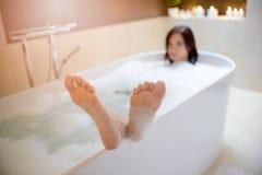 Frau, die Bad mit ihren Füßen am Rand der Badewanne nimmt Stockfotos